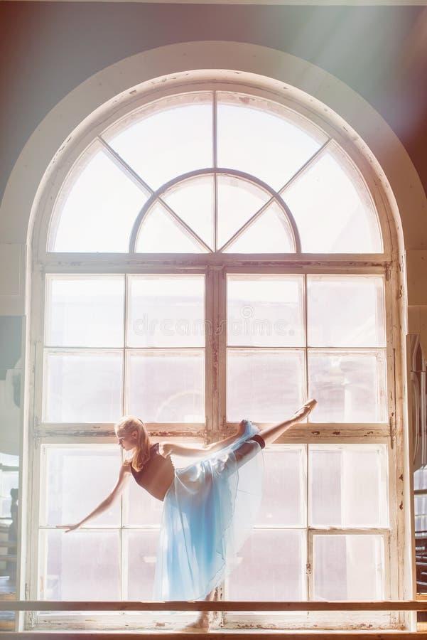 Το Ballerina χορεύει μπροστά από ένα μεγάλο παράθυρο στοκ φωτογραφία