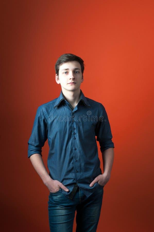 Το Barista στο μπλε πουκάμισο και τα τζιν που στέκονται με παραδίδει τις τσέπες και την εξέταση τη κάμερα στο πορτοκαλί υπόβαθρο στοκ φωτογραφία