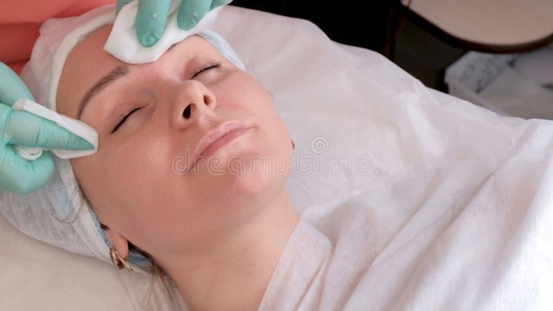 Το Beautician ενυδατώνει το πρόσωπο του κοριτσιού με υγρό σκουπίζει με aloe Το όμορφο κορίτσι με το καθαρό δέρμα παίρνει την ενυδ στοκ εικόνα με δικαίωμα ελεύθερης χρήσης