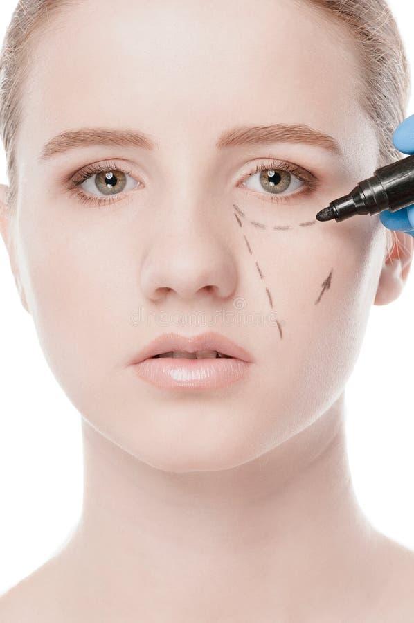 Το Beautician επισύρει την προσοχή τις γραμμές διορθώσεων στο πρόσωπο γυναικών στοκ εικόνα