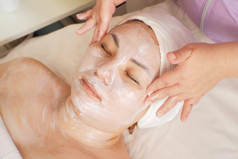 Το Beautician εφαρμόζει μια μάσκα κρέμας στο πρόσωπο του πελάτη Η ενήλικη ασιατική γυναίκα χαλαρώνει το κλείσιμο των ματιών της σ στοκ φωτογραφία με δικαίωμα ελεύθερης χρήσης