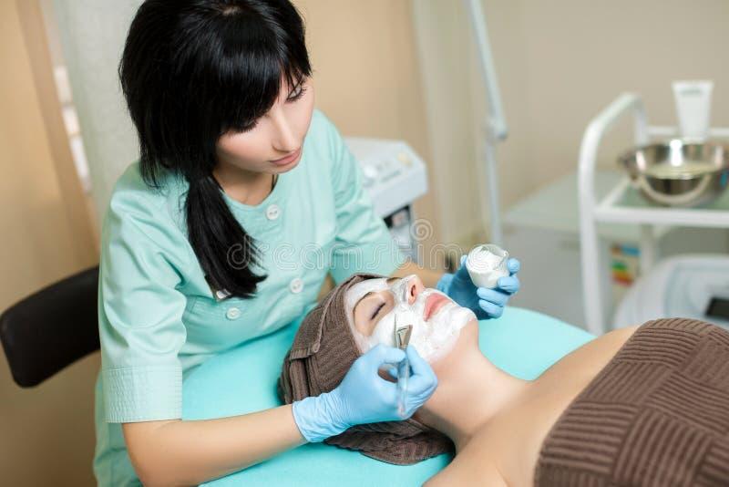 Το Beautician εφαρμόζει τη μάσκα προσώπου στην όμορφη νέα γυναίκα στο σαλόνι SPA καλλυντική φροντίδα δέρματος διαδικασίας E στοκ φωτογραφία με δικαίωμα ελεύθερης χρήσης