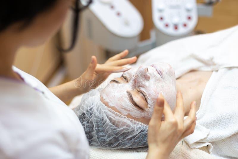 Το Beautician κάνει μια του προσώπου επεξεργασία στη SPA Γυναίκα στη μάσκα στο πρόσωπο στο σαλόνι SPA στοκ φωτογραφία με δικαίωμα ελεύθερης χρήσης