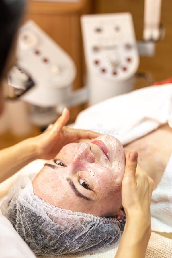 Το Beautician κάνει μια του προσώπου επεξεργασία στο κέντρο SPA Νέα γυναίκα με την του προσώπου καλλυντική επεξεργασία στοκ εικόνα