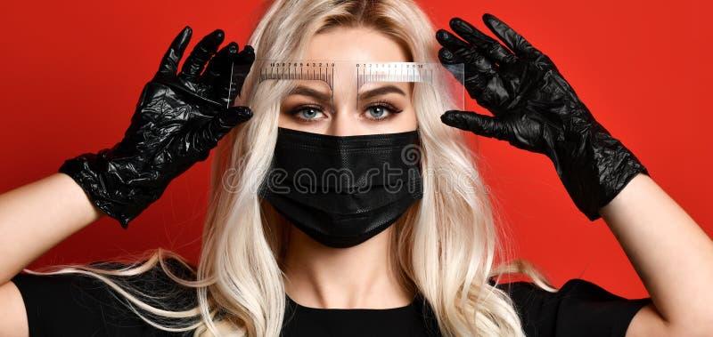 Το Beautician που κάνει διαστίζοντας το φρύδι μόνιμο αποζημιώνει τα φρύδια στα μαύρα γάντια και τη μάσκα στο κόκκινο υπόβαθρο στοκ φωτογραφία