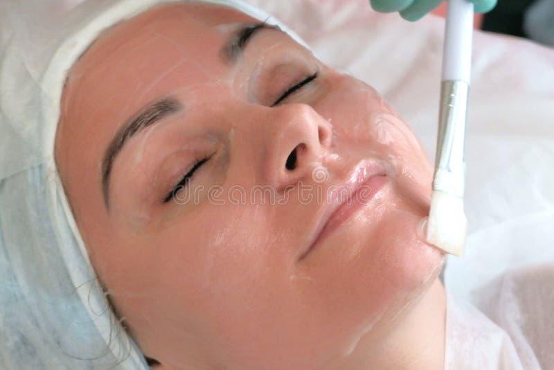 Το Beautician προκαλεί το καθαρίζοντας πήκτωμα στο δέρμα ενός όμορφου κορι στοκ εικόνες