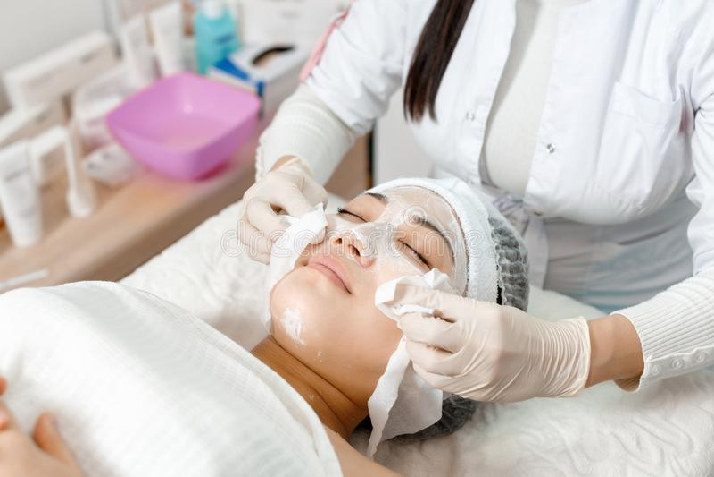 Το Beautician σκουπίζει τη μάσκα από το πρόσωπο στοκ εικόνα