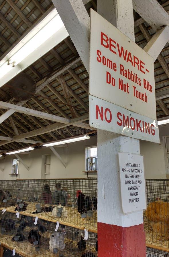Το Beware, μερικά κουνέλια δαγκώνει, δεν αγγίζει, απαγόρευση του καπνίσματος, σημάδι στο κτήριο πουλερικών σε μια δημοφιλή έκθεση στοκ φωτογραφία με δικαίωμα ελεύθερης χρήσης
