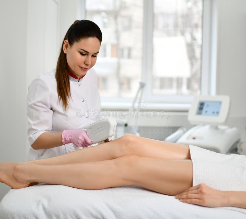 Το brunette γιατρός-Cosmetician εκτελεί μια καλλυντική διαδικασία στα πόδια του ασθενή με την ηλεκτρονική ιατρική συσκευή στην κλ στοκ εικόνες