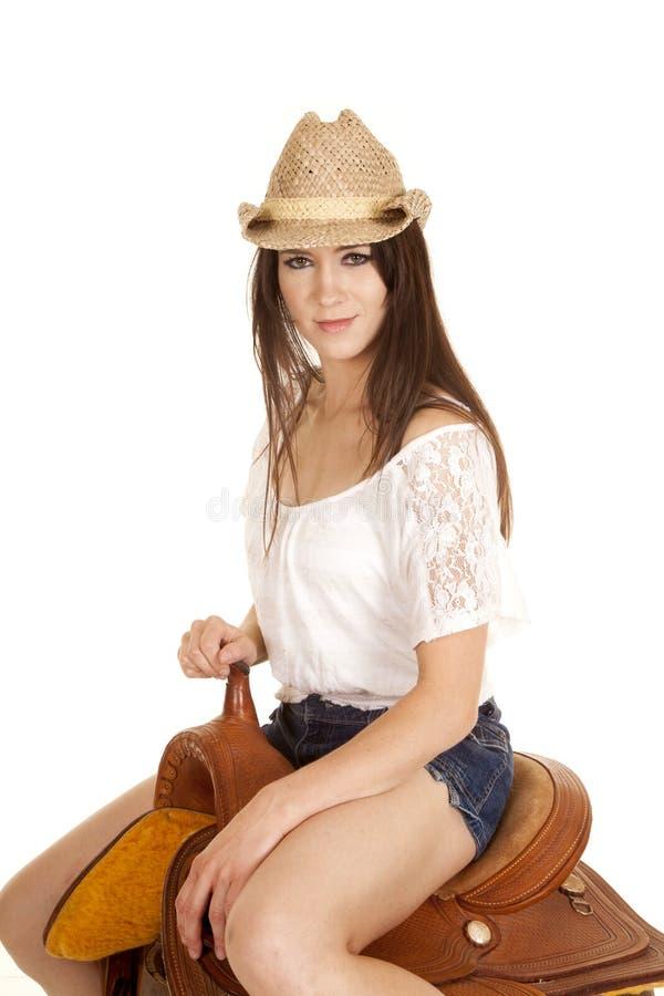 Το Brunette cowgirl κάθεται στη σέλα φαίνεται μικρό χαμόγελο στοκ φωτογραφία με δικαίωμα ελεύθερης χρήσης