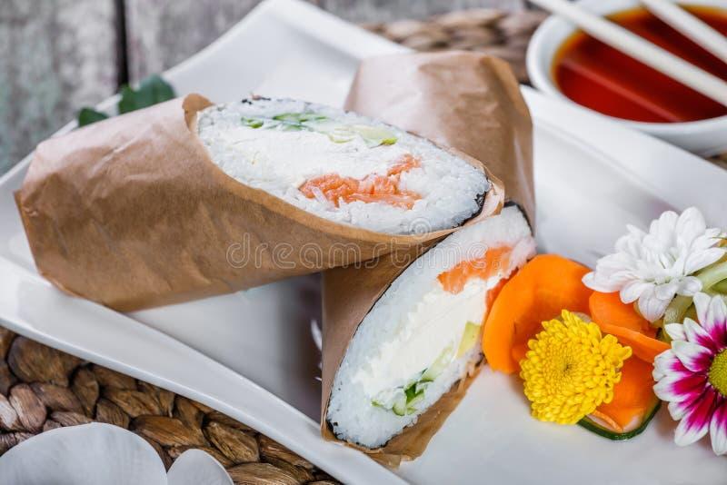 Το burrito σουσιών κυλά με το σολομό, το τυρί κρέμας, το αβοκάντο και το αγγούρι στο πιάτο στοκ φωτογραφίες