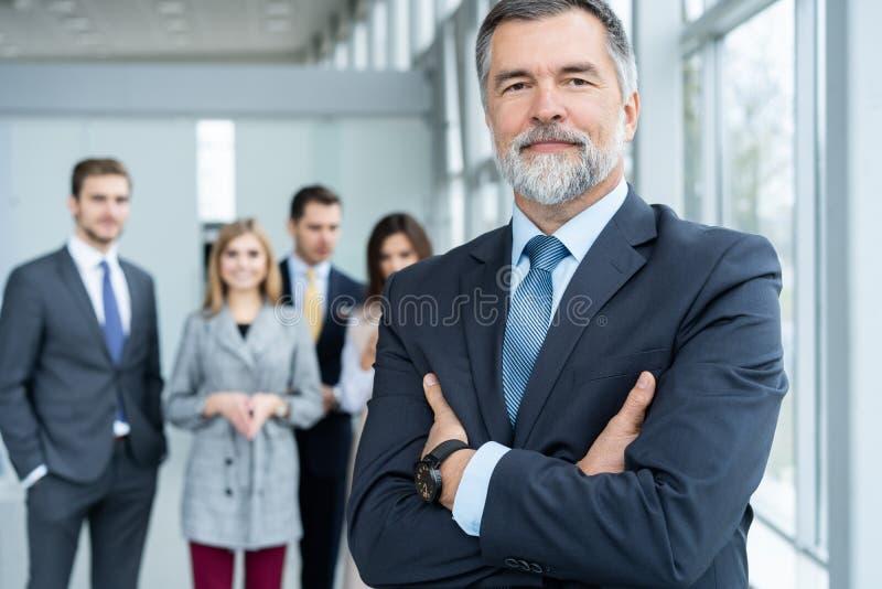 Το Businessteam στην αρχή, ο ευτυχής ανώτερος επιχειρηματίας στο γραφείο του στέκονται μπροστά από την ομάδα τους στοκ εικόνες