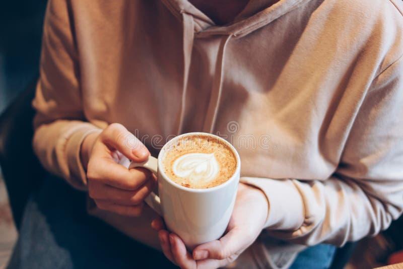 Το cappuccino φλιτζανιών του καφέ με την καρδιά αφρού στα θηλυκά χέρια στον καφέ, κλείνει επάνω στοκ εικόνες