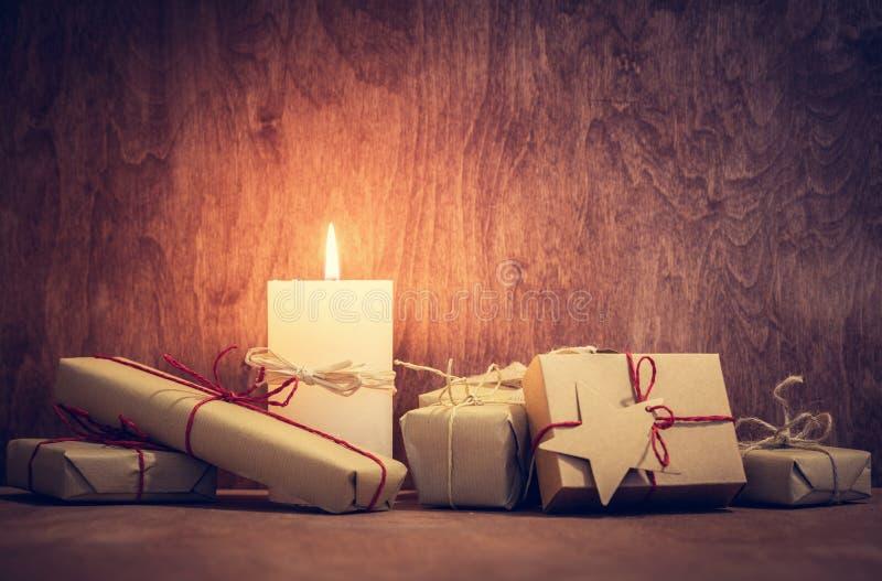 Το Chistmas παρουσιάζει, δώρα με ένα κερί που καίγεται στο ξύλινο υπόβαθρο τοίχων στοκ φωτογραφία με δικαίωμα ελεύθερης χρήσης