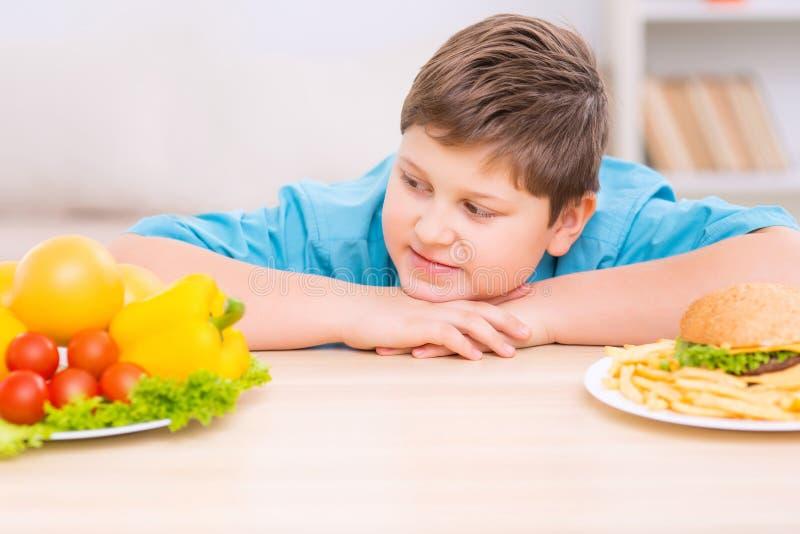 Το Chubby παιδί εξετάζει το υγιές πιάτο τροφίμων στοκ φωτογραφία με δικαίωμα ελεύθερης χρήσης
