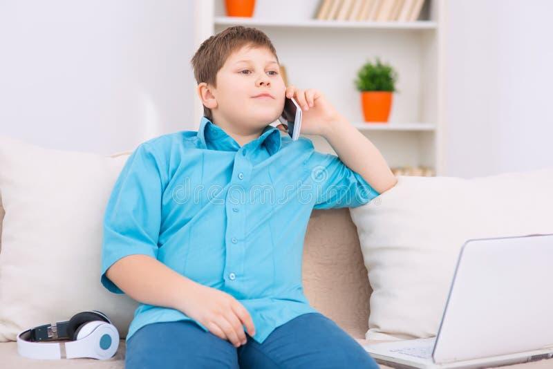 Το Chubby παιδί διοργανώνει μια τηλεφωνική συζήτηση στοκ εικόνες