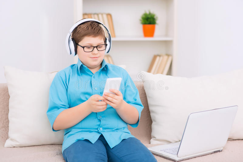 Το Chubby παιδί χρησιμοποιεί το smartphone στοκ εικόνες