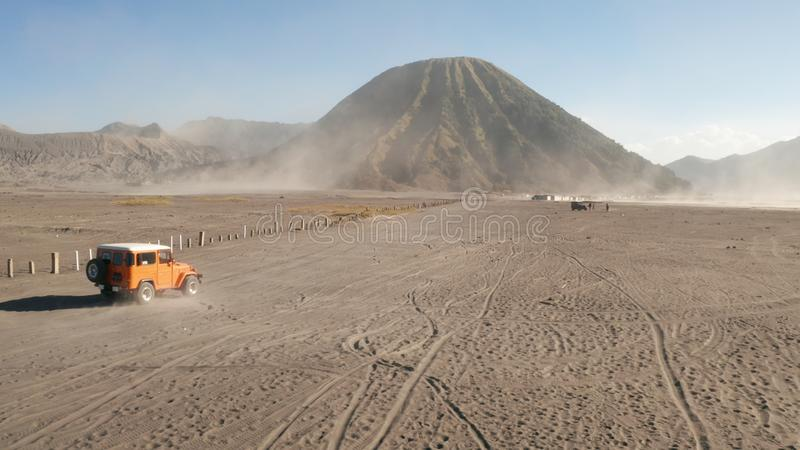 Το Cinematic πυροβόλησε την εναέρια άποψη της κρουαζιέρας τζιπ γύρου στο όμορφο ηφαίστειο Bromo υποστηριγμάτων με την έρημο στην  στοκ εικόνες