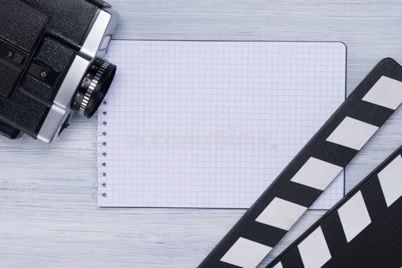 Το Clapperboard, camcorder και το σημειωματάριο για τα αρχεία είναι στο ελαφρύ υπόβαθρο του πίνακα του διευθυντή στοκ εικόνες με δικαίωμα ελεύθερης χρήσης