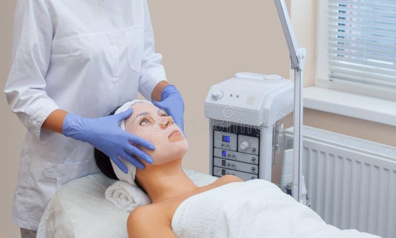 Το cosmetologist για τη διαδικασία και το δέρμα, που εφαρμόζει μια μάσκα φύλλων στο πρόσωπο μιας νέας γυναίκας στοκ εικόνες με δικαίωμα ελεύθερης χρήσης