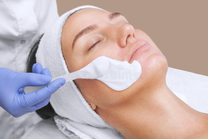 Το cosmetologist για τη διαδικασία και το δέρμα, που εφαρμόζει μια των φυκών μάσκα στο πρόσωπο μιας νέας γυναίκας είναι στοκ εικόνα