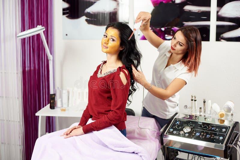 Το Cosmetologist δίνει την επεξεργασία τρίχας σε έναν πελάτη brunette με μια χρυσή μάσκα στο πρόσωπό της σε ένα σύγχρονο σαλόνι ο στοκ φωτογραφία