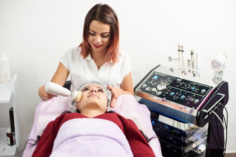 Το Cosmetologist κάνει το υλικό διαδικασίας να αντιμετωπίσει τον καθαρισμό με τη μαλακή περιστρεφόμενη βούρτσα στοκ εικόνα με δικαίωμα ελεύθερης χρήσης