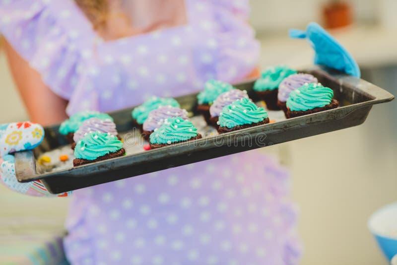 Το Cupcakes είναι στο δίσκο Θηλυκά χέρια που κρατούν το επιδόρπιο στοκ εικόνες