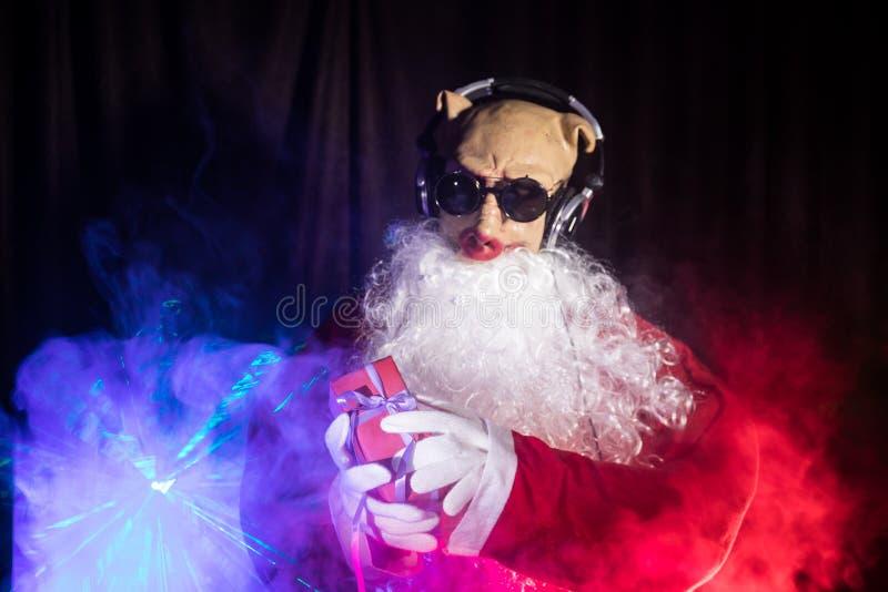 Το DJ Άγιος Βασίλης στα Χριστούγεννα με τα γυαλιά και το χιόνι αναμιγνύουν στο γεγονός Παραμονής Πρωτοχρονιάς στις ακτίνες του φω στοκ φωτογραφίες με δικαίωμα ελεύθερης χρήσης