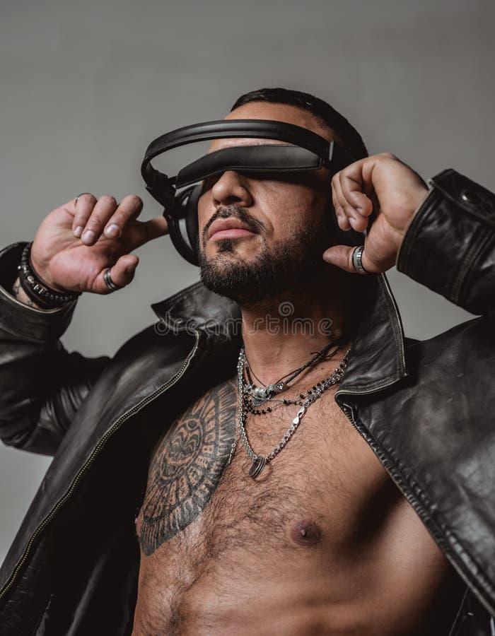 Το DJ αρχίζει αυτό το κόμμα Μυϊκό αθλητικό προκλητικό αρσενικό με τα ακουστικά Βέβαια και όμορφη βάναυση μουσική ακούσματος ατόμω στοκ εικόνες με δικαίωμα ελεύθερης χρήσης