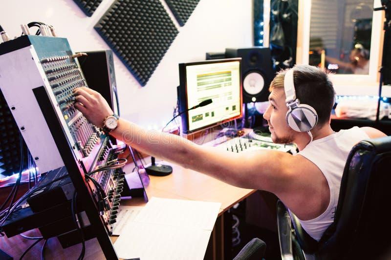 Το DJ ρυθμίζει τον εξοπλισμό στο στούντιο υγιούς καταγραφής στοκ εικόνες