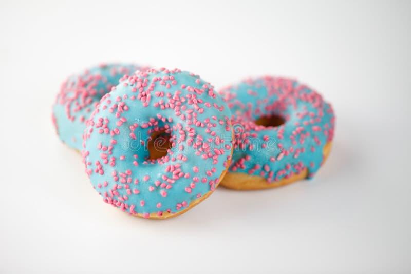 Το Donuts με το μπλε λούστρο και το ροζ ψεκάζει στο άσπρο υπόβαθρο Τοπ όψη στοκ εικόνα με δικαίωμα ελεύθερης χρήσης