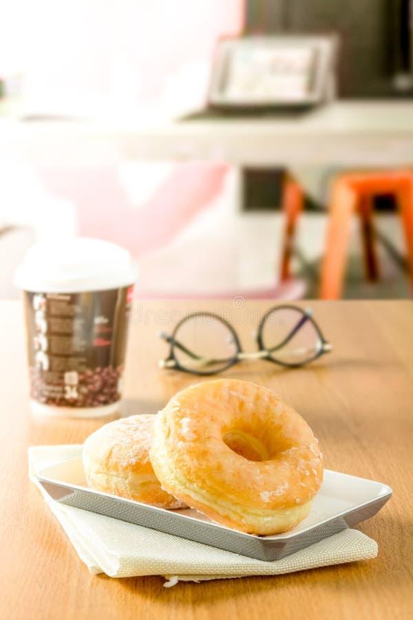 Το Donuts στο πιάτο με το φλυτζάνι και τα γυαλιά καφέ στον πίνακα στα ξημερώματα στο γραφείο είναι θολωμένο στο υπόβαθρο στοκ εικόνα με δικαίωμα ελεύθερης χρήσης