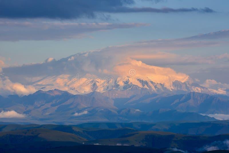 Το Elbrus στο ηλιοβασίλεμα καλύπτεται με ένα καπέλο των σύννεφων Elbrus στο ηλιοβασίλεμα στοκ εικόνες με δικαίωμα ελεύθερης χρήσης