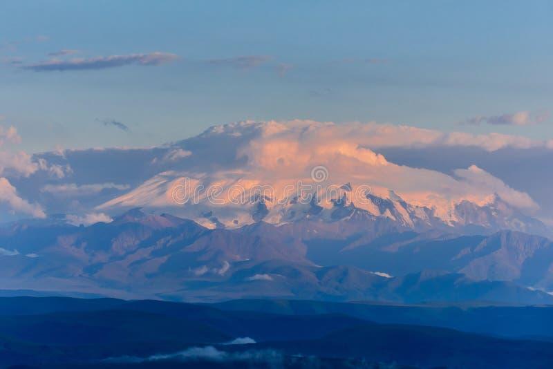 Το Elbrus στο ηλιοβασίλεμα καλύπτεται με ένα καπέλο των σύννεφων Elbrus στο ηλιοβασίλεμα στοκ εικόνα