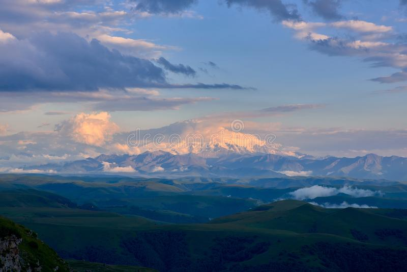 Το Elbrus στο ηλιοβασίλεμα καλύπτεται με ένα καπέλο των σύννεφων Elbrus στο ηλιοβασίλεμα στοκ εικόνες