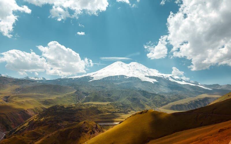 Το Elbrus τοποθετεί και πράσινοι λόφοι στις θερινές ημέρες Περιοχή Elbrus, του βόρειου Καύκασου, Ρωσία στοκ φωτογραφία με δικαίωμα ελεύθερης χρήσης