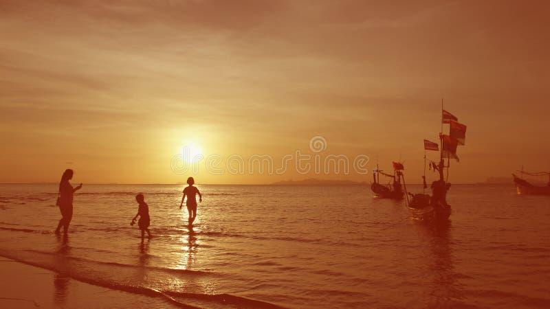 Το Familly χαλαρώνει ενώ ηλιοβασίλεμα από την παραλία στοκ εικόνες