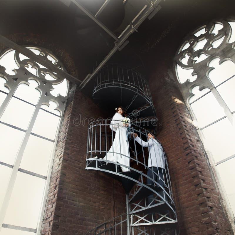 Το Fiance βοηθά τη νύφη για να πάει κάτω στα σπειροειδή σκαλοπάτια παλαιό σε γοτθικό στοκ φωτογραφίες με δικαίωμα ελεύθερης χρήσης