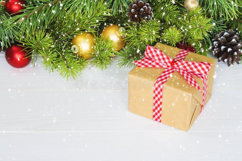 Το FIR διακλαδίζεται με τις διακοσμήσεις - κιβώτιο δώρων, ελαιόπρινος κώνων πεύκων και μπιχλιμπίδια Υπόβαθρο Χριστουγέννων, διάστ στοκ εικόνες