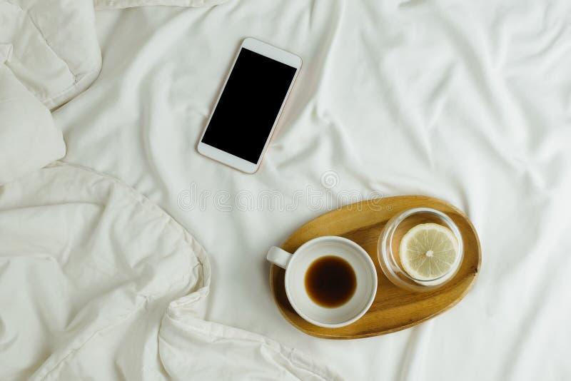 Το Flatlay του φλιτζανιού του καφέ και το λεμόνι ποτίζουν στον ξύλινους δίσκο και το smartphone με τη μαύρη οθόνη στοκ φωτογραφία