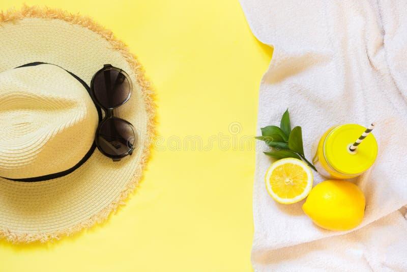 Το foman ` s καπέλο αχύρου, τα γυαλιά ήλιων και το εξάρτημα παραλιών με το citrics detox ποτίζουν σε κίτρινο Τοπ όψη Επίπεδος βάλ στοκ εικόνες