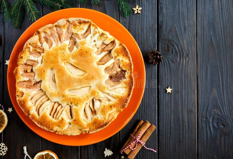 Το Fruitcake για τα Χριστούγεννα διακόσμησε με τα μήλα στο πορτοκαλί πιάτο στον καφετή ξύλινο πίνακα Σπιτική ζύμη Delicioius νέο  στοκ εικόνες