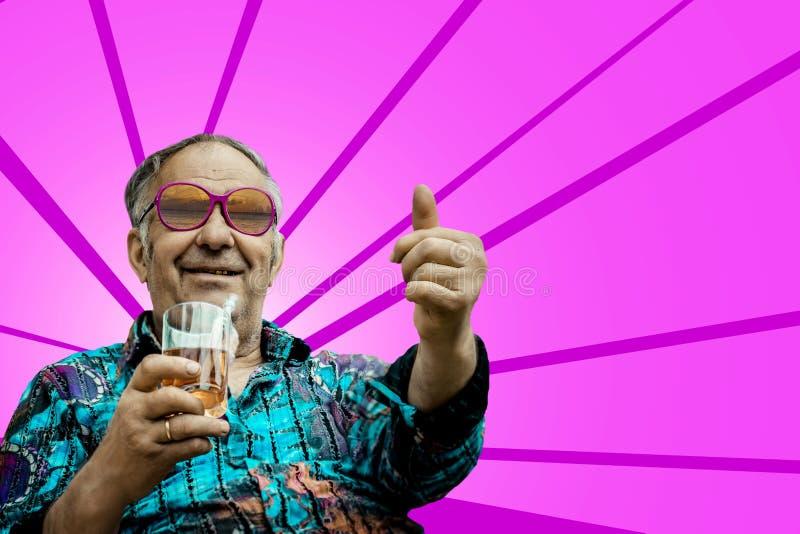 Το Grandpa παρουσιάζει αντίχειρα στο ρόδινο υπόβαθρο στοκ εικόνες