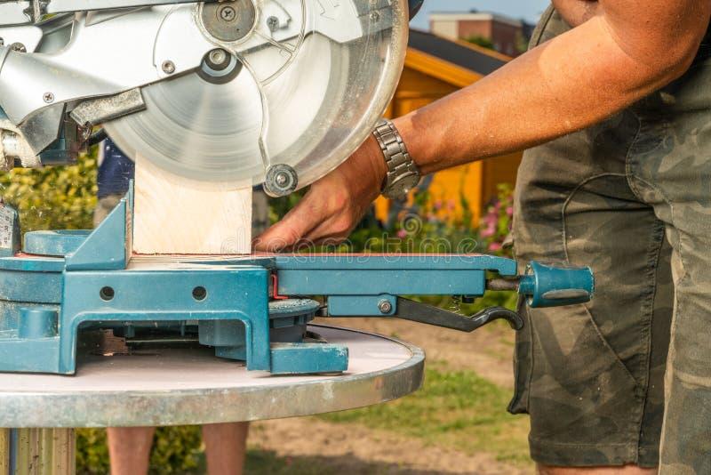 Το Handyman είδε μια ξύλινη ακτίνα με ένα κυκλικό πριόνι χωρίς προστατευτικό εξοπλισμό στοκ εικόνες
