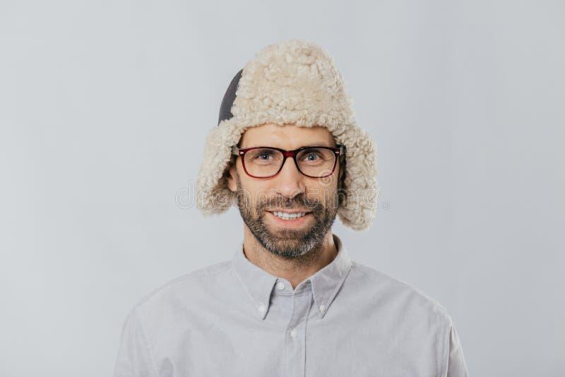 Το Headshot του εύθυμου όμορφου καυκάσιου τύπου φορά το θερμό χειμώνα ΚΑΠ με τα earflaps, θεάματα και το άσπρο πουκάμισο, εξετάζε στοκ φωτογραφία