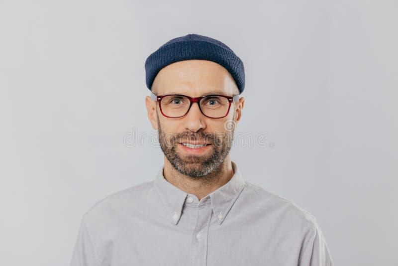 Το Headshot του όμορφου αξύριστου ατόμου φορά τα διαφανή γυαλιά, κάλυμμα, επίσημο πουκάμισο, εξετάζει άμεσα τη κάμερα, που απομον στοκ φωτογραφίες