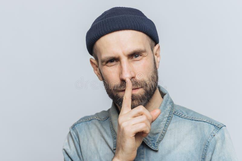 Το Headshot του όμορφου ατόμου με την παχιά γενειάδα και mustache, έχει το μυστικό να κοιτάξει, καταδεικνύει το σημάδι σιωπής, ζη στοκ εικόνες