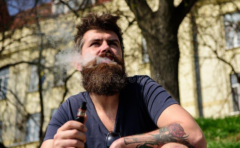 Το Hipster με η τρίχα και γκρίζος στο χαλαρωμένο ονειροπόλο πρόσωπο με τον άσπρο καπνό που πετά από το στόμα Vaping και συνήθειες στοκ φωτογραφία με δικαίωμα ελεύθερης χρήσης