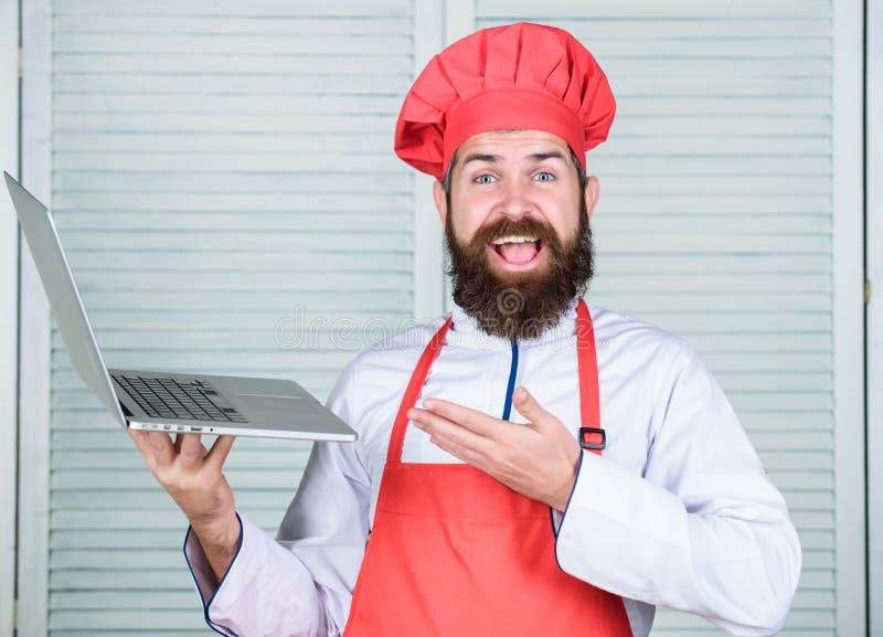 Το Hipster στο καπέλο και η ποδιά αγοράζουν τα προϊόντα on-line Να ψωνίσει on-line r Αρχιμάγειρας ατόμων που ψάχνει τα σε απευθεί στοκ φωτογραφία